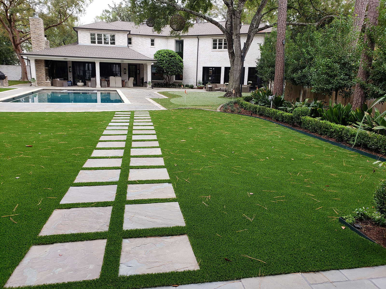 beautiful backyard with artificial grass and pavers - golf green